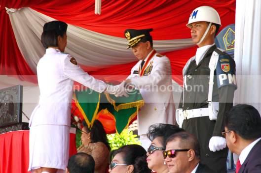 PEMBAWA BAKI. Christin Matindas, siswa SMA Negeri 1 Tomohon, kelahiran 2 September 1997 sebagai pembawa baki bendera, sedang menerima Bendera Merah Putih dari tangan Gubernur Sulawesi Utara, SH Sarundajang.