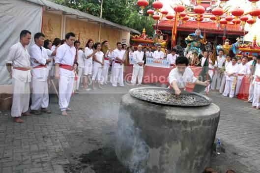Umat Tridharma melakukan ritual masak minyak dalam peringatan kelahiran Kwan Seng Ta Tie Kwan Kong di Klenteng Kwan Kong, Manado, Sulawesi Utara, 31 Juli 2013.