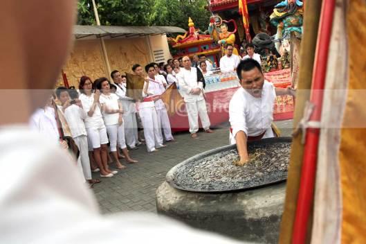 Salah satu umat Tridharma mencelupkan tangannya ke dalam minyak yang sedang mendidik dalam ritual masak minyak dalam peringatan kelahiran Kwan Seng Ta Tie Kwan Kong di Klenteng Kwan Kong, Manado, Sulawesi Utara, 31 Juli 2013.