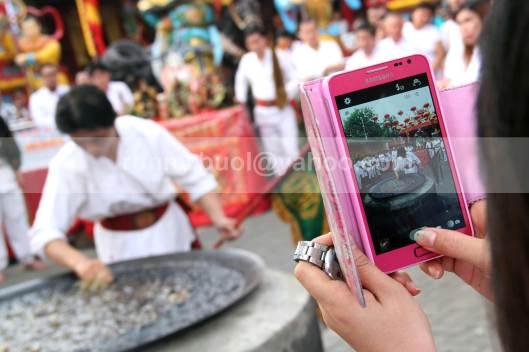 Warga mengabadikan salah satu umat Tridharma yang sedang mencelupkan tangannya ke dalam minyak yang sedang mendidik dalam ritual masak minyak dalam peringatan kelahiran Kwan Seng Ta Tie Kwan Kong di Klenteng Kwan Kong, Manado, Sulawesi Utara, 31 Juli 2013.