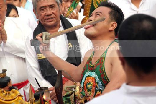 Titisan Dewa Kwang Kong sedang melaksanakan ritual  masak minyak memperingati kelahiran Kwan Seng Ta Tie Kwan Kong di Klenteng Kwan Kong, Manado, Sulawesi Utara, 31 Juli 2013.