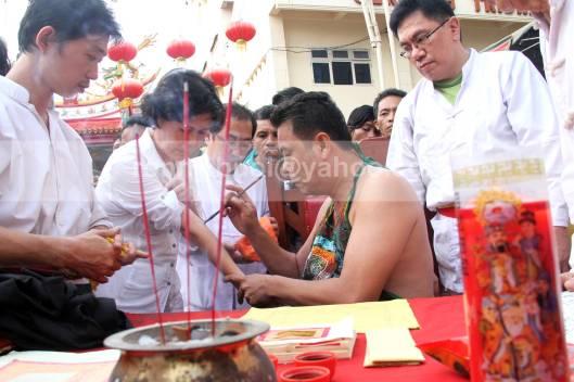 Umat Tridharma meminta pentunjuk pada titisan dewa dalam ritula masak minyak memperingati kelahiran Kwan Seng Ta Tie Kwan Kong di Klenteng Kwan Kong, Manado, Sulawesi Utara, 31 Juli 2013.