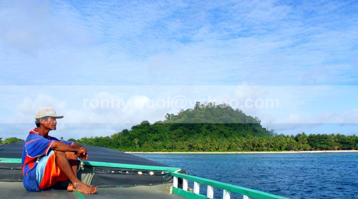 MENUJU PULAU -- Lelaki separuh baya ini sedang membantu Joki (tidak terlihat)  sebuah perahu motor yang berlayar ke Pulau Lihaga. Sebuah pulau di Minahasa Utara yang merupakan salah satu destinasi wisata di Sulawesi Utara. 7D | 18-135mm | F/16 | Av Mode | ISO 250