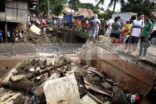 Warga menyaksikan puing bekas terjangan banjir di tepi Sungai Palaus di Desa Lowu 1.