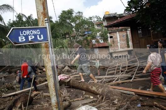 Warga datang melihat akibat yang ditimbulkan banjir bandang di Desa Lowu Utara.
