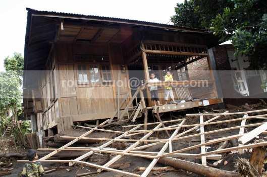 Dua orang anak berada di sebuah rumah yang nyaris terseret banjir bandang di Desa Lowu Utara.