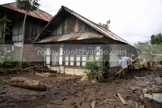 Seorang warga mencoba menyingkirkan lumpur yang sangat tebal di rumahnya yang ikut terkena dampak banjir bandang di Desa Lowu 1.