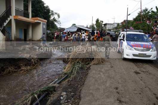 Aparat kepolisian dan TNI ikut membantu warga membersihkan bekas terjangan banjir bandang.