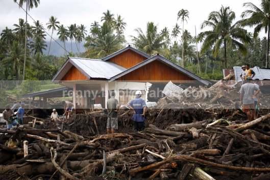 Warga di Desa Rasi mencari korban Yanti Dili (11) yang terseret banjir bandang.