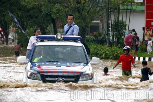 BANTU EVAKUASI - Polisi lalu lintas membantu evakuasi siswa yang terjebak banjir bandang di daerah Tikala, 15 Januari 2014.