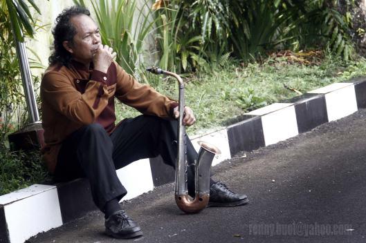 MENUNGGU PENTAS.  Salah satu anggota Musik Bambu Klarinet sedang menunggu waktu pentas, ketika group musiknya diundang sebagai pengisi acara sewaktu Kapolri Jendral Polisi Sutarman mengunjungi Manado, 21 Februari 2014. Musik bambu merupakan salah satu musik traditional Sulawesi Utara yang instrumennya terbuat dari bambu. Namun seiring perkembangan waktu, musik ini kemudian dipadukan dengan berbagai alat musik modern seperti Saxophone dan drum.