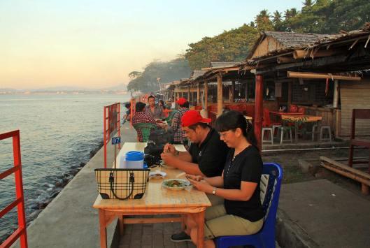 Pengunjung sedang menikmati kuliner di Sabua Buluh pantai Malalayang. / Foto: Ronny A. Buol