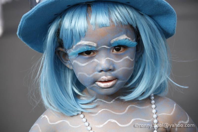 Peserta cilik Fashion Carnaval mengecat wajahnya dengan warna yang selaras dengan busana yang digunakannya.