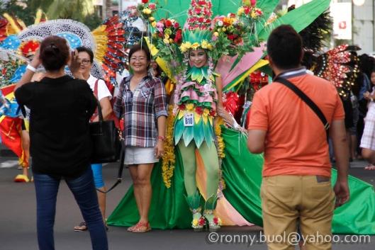 Penonton Fashion Carnaval mengambil kesempatan berpose dengan peserta parade yang digelar melintas di Kawasan Mega Mas, Manado, Sabtu (29/1/2016).