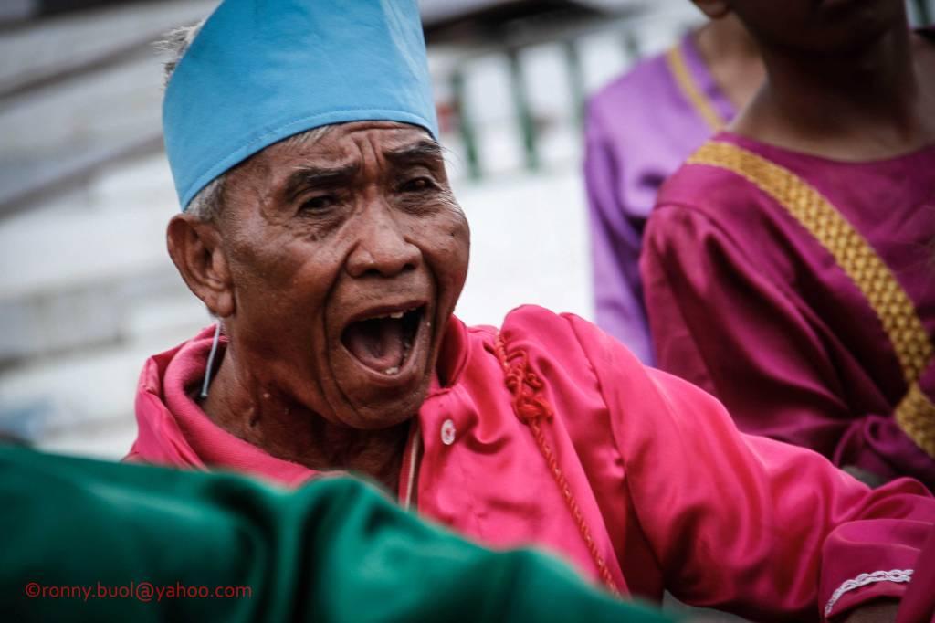 Julius Kalinge (77), warga Teling, Manado, asal Tamako, Sagihe sedang mengekspresikan nyanyian daerah sambil memainkan alat musik Tangonggong dalam Gelar Upacara Adat Tulude yang diselanggarakan oleh Dinas Kebudayaan dan Pariwisata Sulawesi Utara yang bekerjasama dengan berbagai Komunitas Masyarakat Nusa Utara, Sabtu (6/2/2016) di Lapangan KONI Manado.