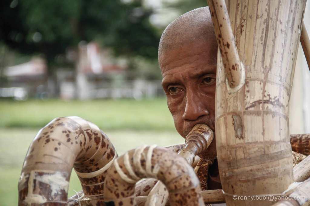 Salah satu pemain musik tiup tradisional yang terbuat dari bambu, sedang membawakan lagu pada Gelar Upacara Adat Tulude yang diselanggarakan oleh Dinas Kebudayaan dan Pariwisata Sulawesi Utara yang bekerjasama dengan berbagai Komunitas Masyarakat Nusa Utara, Sabtu (6/2/2016) di Lapangan KONI Manado.