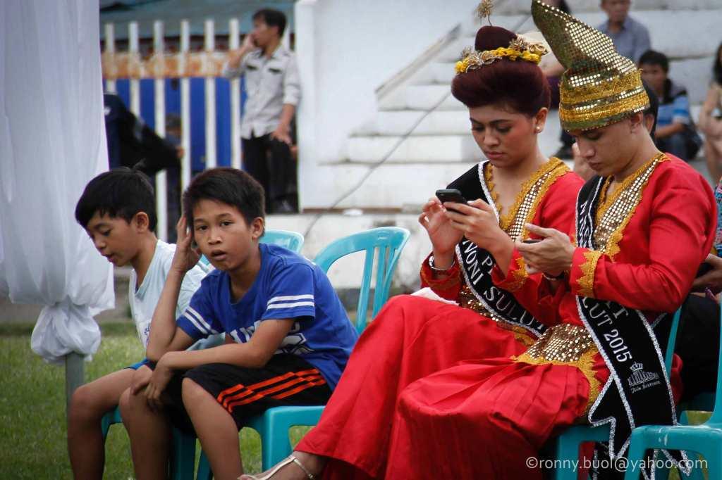Dua orang dengan pakaian daerah mengisi menyibukkan diri dengan gadget di sela-sela event Gelar Upacara Adat Tulude yang diselanggarakan oleh Dinas Kebudayaan dan Pariwisata Sulawesi Utara yang bekerjasama dengan berbagai Komunitas Masyarakat Nusa Utara, Sabtu (6/2/2016) di Lapangan KONI Manado.