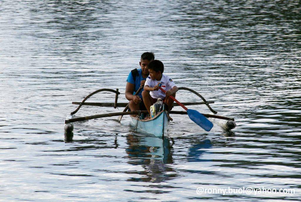MENDAYUNG - Dua pelajar ini harus mendayung perahu menyeberangi lautan untuk menuju sekolah mereka di Pulau Batuwingkung, Sangihe.