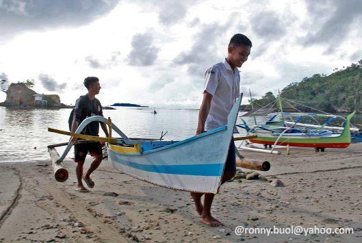 ANGKAT - Para pelajar di pulau Batuwingkung, Sangihe saling membantu mengangkat perahu yang mereka gunakan untuk pergi ke sekolah.