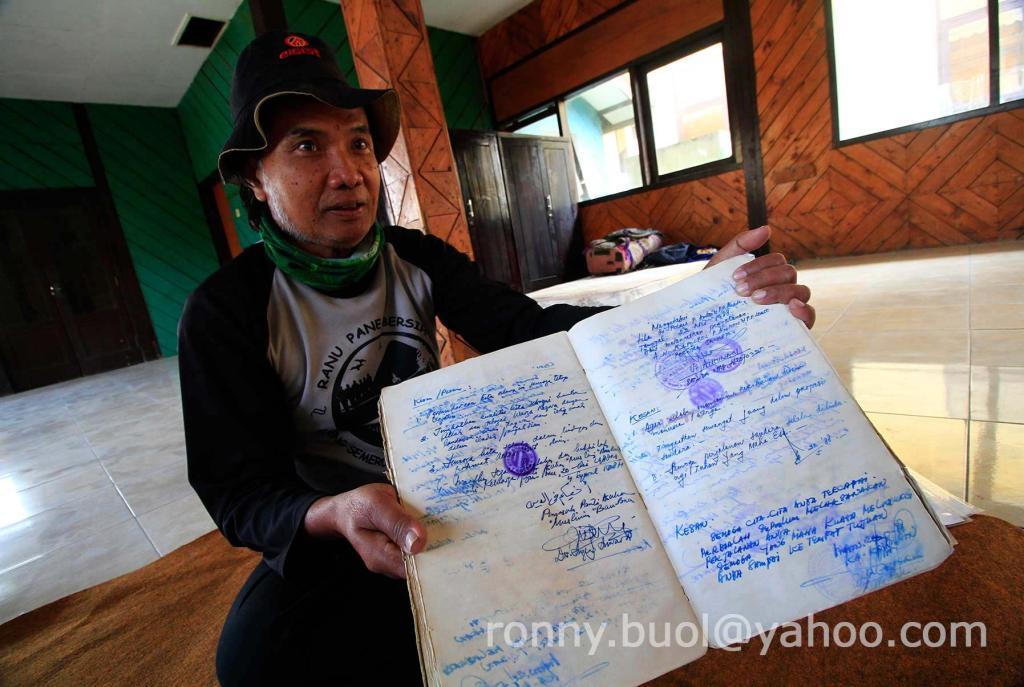 BUKTI -- Hambali menunjukkan sebagian lembaran buku albumnya berisi tandantangan dan cap dari pemerintah setempat di daerah yang dia kunjungi.